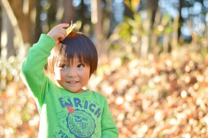 子供が頭に枯葉を乗せている